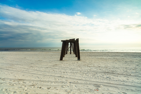panama city beach: The skeletal remains of an old wooden pier on a Florida panhandle beach in the late afternoon.