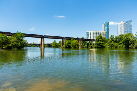 Skyline view of downtown Austin, Texas with the Colorado River and kayaker cruising by.