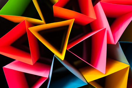 Colorful card stock in unique triangular shapes with shadow effect and selective focus on a black background.