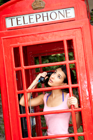 Beautiful young woman in a telephone booth Stock Photo