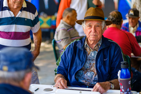octogenarian: Miami, FL USA - January 11, 2017: Unidentified elderly man plays the domino game in the historic Domino Park in popular Little Havana.