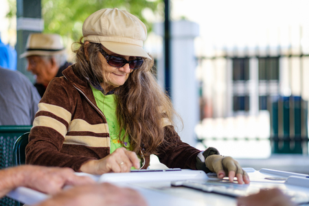 octogenarian: Miami, FL USA - January 11, 2017: Unidentified elderly woman in deep concentration as she plays the domino game in the historic Domino Park in popular Little Havana. Editorial
