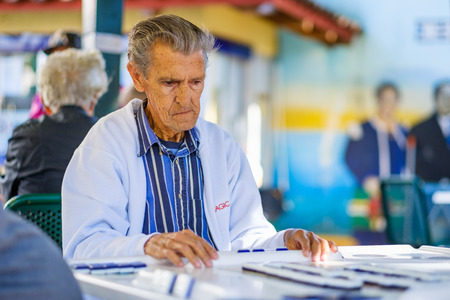 octogenarian: Miami, FL USA - January 11, 2017: Unidentified elderly man in deep concentration as he plays the domino game in the historic Domino Park in popular Little Havana.