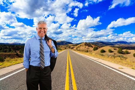 青空: Handsome middle age business man standing on a desert highway.