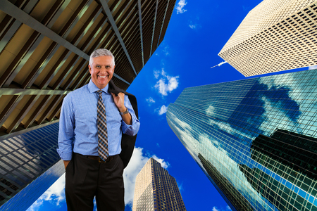 Handsome middle age business man with a downtown urban skyscraper background. Stock Photo