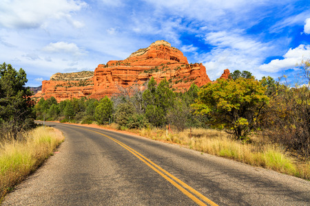 Highway view of the natural beauty of the Arizona desert with majestic sandstone buttes. Фото со стока