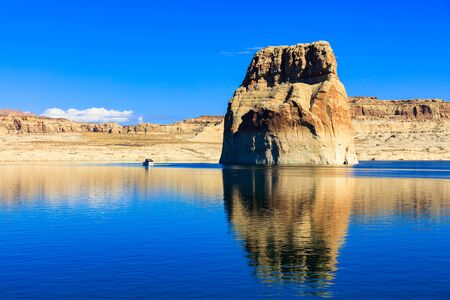 The natural beauty of Lone Rock Canyon and Lake Powell in Utah with yacht cruising by.