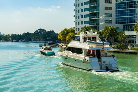 Miami Beach, FL USA - February 13, 2017: Luxury yachts cruising along the intracoastal waterway for display at the popular Miami International Boat Show.