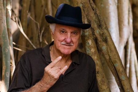 Elderly handsome man outdoor portrait wearing a bowler hat. Stock Photo