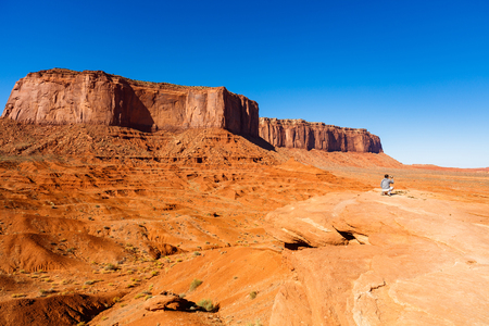 Monument Valley, Utah USA - November 2, 2016: A visitor enjoying the natural beauty of the red sandstone buttes in this popular tourist destination.