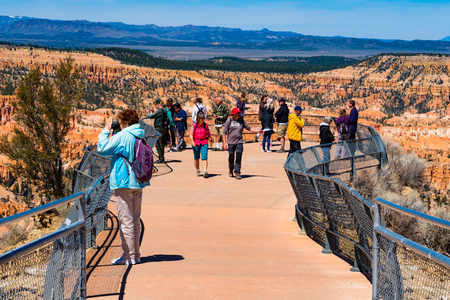 Bryce Canyon, Utah USA - April 22, 2017: Visitors enjoying the natural beauty of the Amphitheater from an observation point in Bryce Canyon National Park.