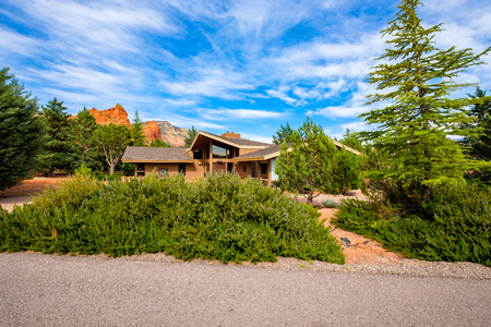 Sedona, Arizona USA - April 23, 2017: Typical modern desert home with majestic red rock formations in the background in popular Sedona.