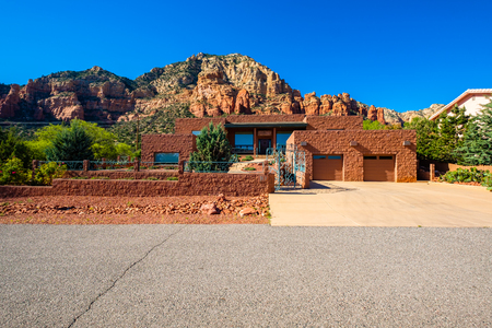 Sedona, Arizona USA - April 25, 2017: Typical modern adobe style architecture desert home with majestic red rock formations in the background in popular Sedona.