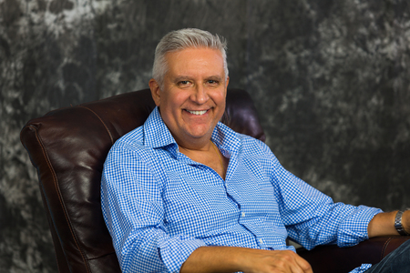 Handsome middle age man sitting on a leather recliner with a gray background.