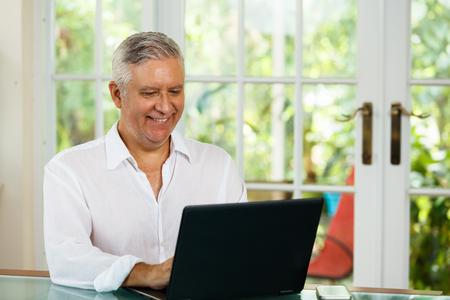Knappe portret van middelbare leeftijd in een thuis omgeving met een laptop.