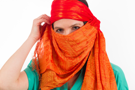 Pretty woman covered by a orange colored veil on a white background.