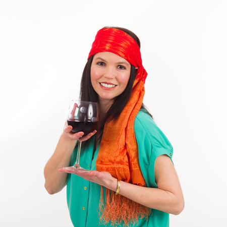 Pretty middle age woman wearing a colorful bandana holding a glass of red wine on a white background.