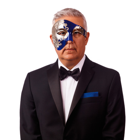 Handsome middle age man with tuxedo and masquerade mask on a white background.