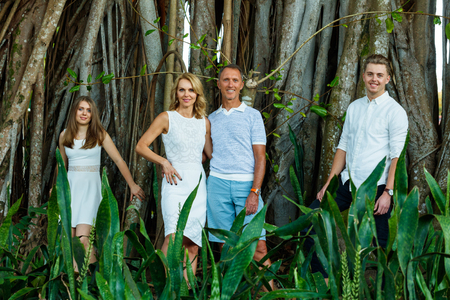 Mother, Father, son and daughter outdoor lifestyle portrait in a park setting.