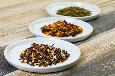 Close up view of herbal tea blends on white plates and a wood table.