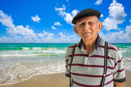 Elderly 80 plus year old man outdoor portrait with a beach background.