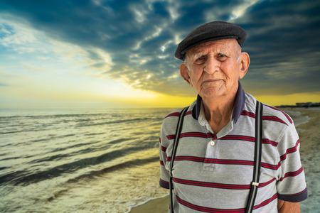 Elderly 80 plus year old man outdoor portrait enjoying the beach at sunset. Stock Photo