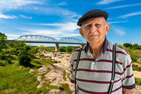 Elderly 80 plus year old man outdoor portrait with a vintage bridge in the background.