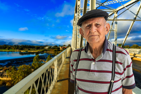 Elderly 80 plus year old man outdoor portrait standing in the road with a vintage bridge in the background.