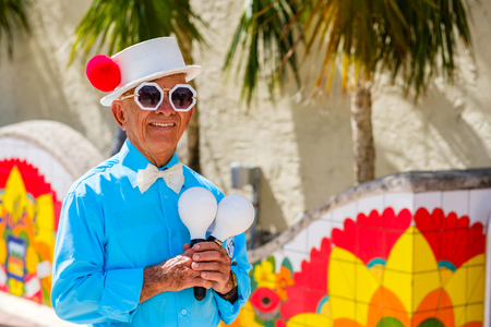 Miami, Florida - February 12, 2018: Unidentified elderly street performer in costume holding maracas along Southwest eight street in popular Little Havana. 에디토리얼