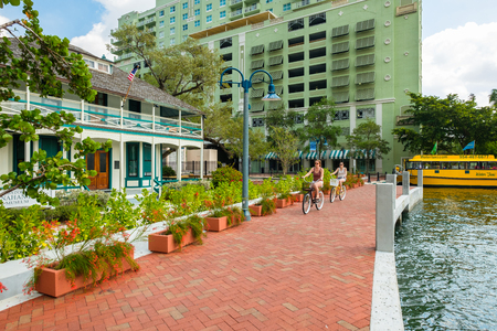 Fort Lauderdale, Florida - March 20, 2018: Cityscape view of the popular Las Olas Riverwalk downtown district with visitors riding bicycles along the promenade. Editorial