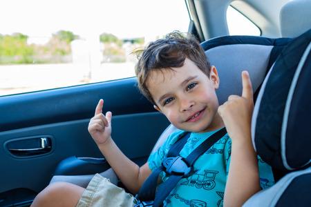 Cute boy sitting in a car seat. Banco de Imagens