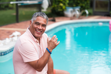 Handsome middle age hispanic man outdoor lifestyle by a swimming pool in a home setting. Stock fotó