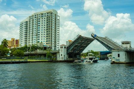 Miami, Florida USA - July 8, 2018: Scenic Miami River cityscape with boats cruising under the West Flagler Street drawbridge. Editöryel