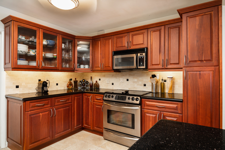 Traditional cheery wood cabinet home kitchen with a black granite countertop. Stock Photo