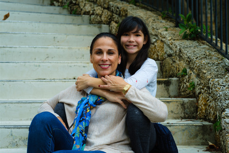 Mother with pre teenage daughter outdoor portrait.