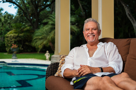 Handsome middle age man outdoor portrait in a home swimming pool patio setting.
