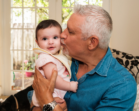 Grandfather with beautiful five month old baby granddaughter portrait in a home setting. 免版税图像