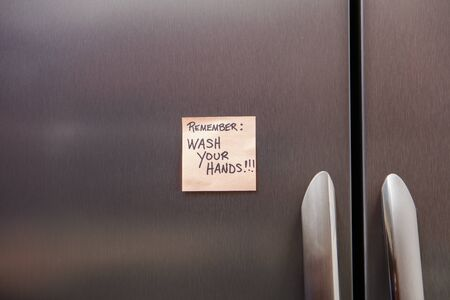 Close up view of a sticky note on a home refrigerator about the coronavirus.