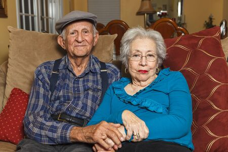 Senior eighty plus year old couple in an affectionate pose in a home setting.