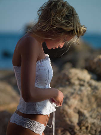 young woman in a corset is on the beach