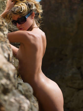 beautiful nude woman standing near a rock on the beach