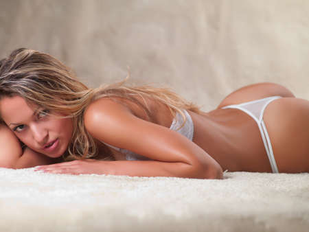 A young woman in underwear lying on the carpet Stock Photo