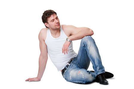 young man in jeans sitting on an isolated background Stock Photo