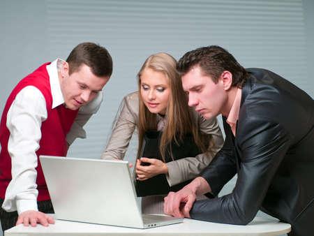 Dos hombres y una mujer trabajando con un equipo en la Oficina Foto de archivo - 9336192