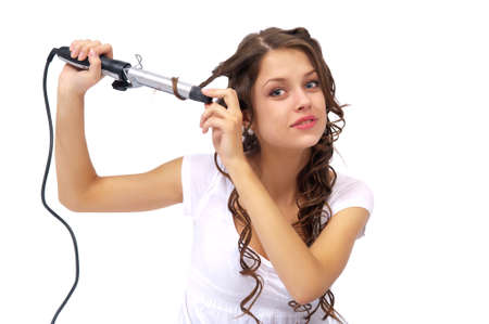 girl with curly hair biting hair dryer. Isolated background