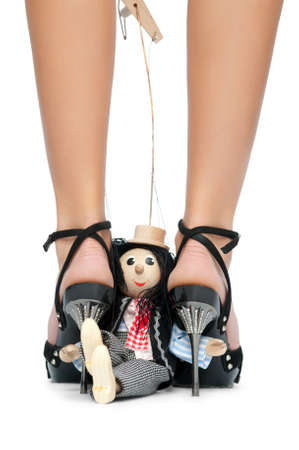 Toy puppet sits near the feet of a young woman. Isolated background photo
