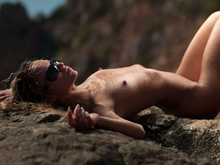Nude woman in water droplets lying on a rock
