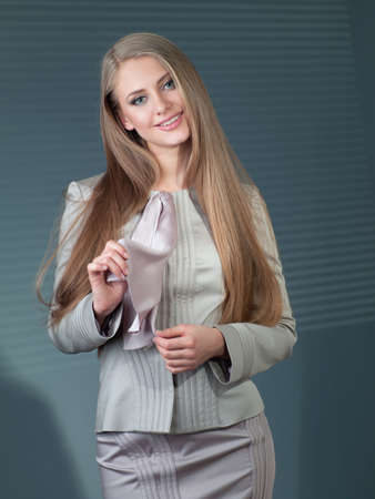 beautiful woman in a gray suit against a dark background in the office Stock Photo