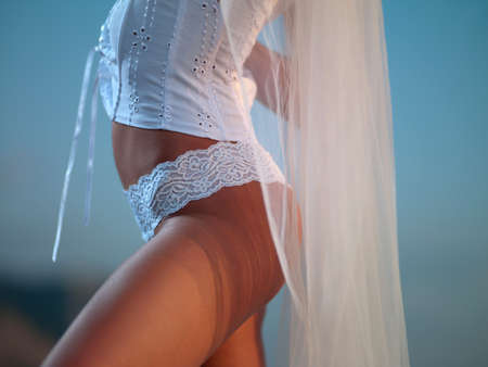 beautiful young woman in a white corset and underwear stands on the beach Stock Photo