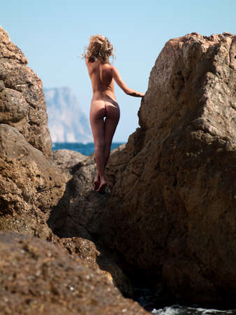 naked woman in the droplets of water standing on a rock Stock Photo